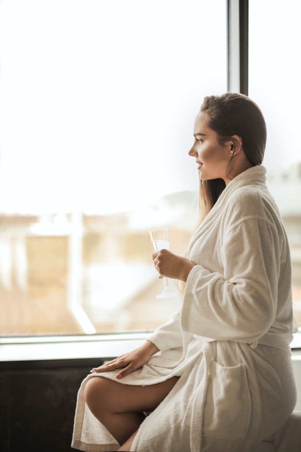 woman drinking alone in white robe gazing out the window